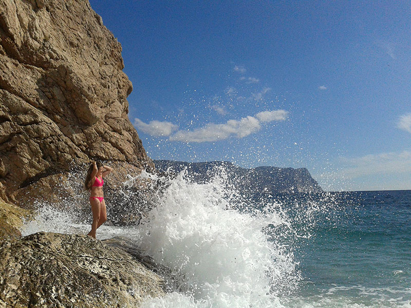 Девушка в брызгах волн на пляже Васили в Севастополе в Крыму