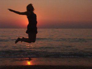 Девушка прыгает на фоне заката и моря