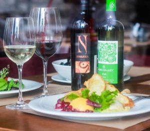 Вино в бокалах и в бутылках на столе