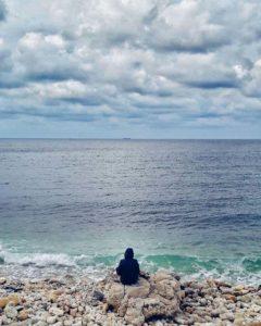 Человек сидит у моря