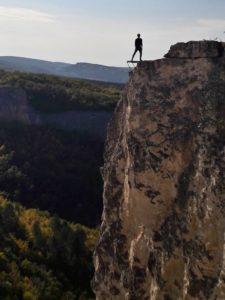 Мужчина стоит на мостике над обрывом на Сюйреньской крепости в Крыму