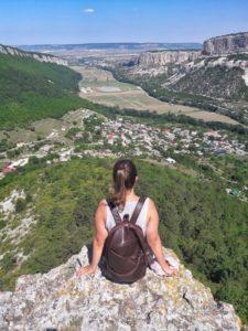 Девушка сидит на обрыве на Сюйреньской крепости в Крыму и смотрит на долину